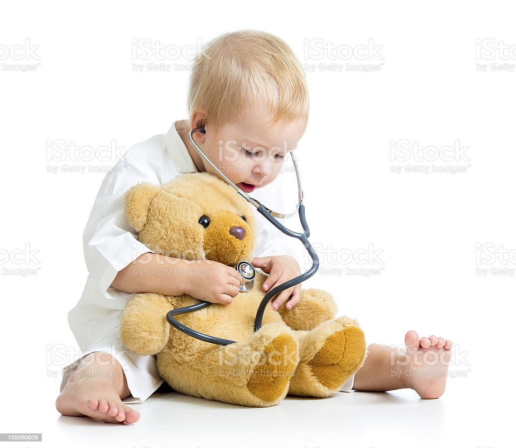 Adorable child with clothes of doctor and teddy bear toy stock photo