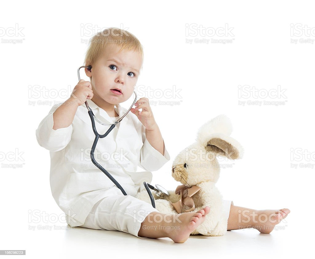 Adorable child with clothes of doctor examining hare toy stock photo