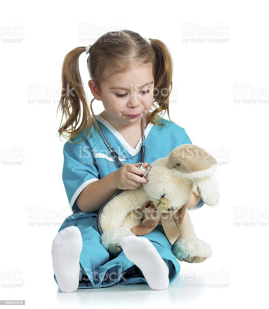 Adorable child with clothes of doctor examining toy stock photo