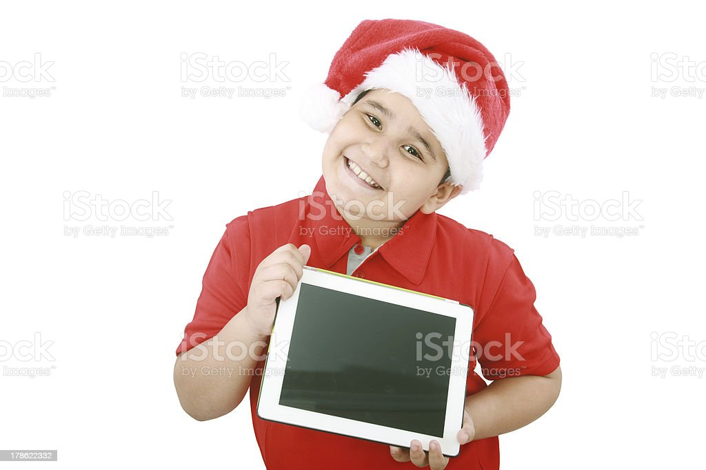 Adorable child with Santa hat offering a tablet royalty-free stock photo