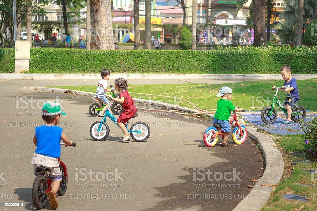 adorable children riding their bikes in park stock photo