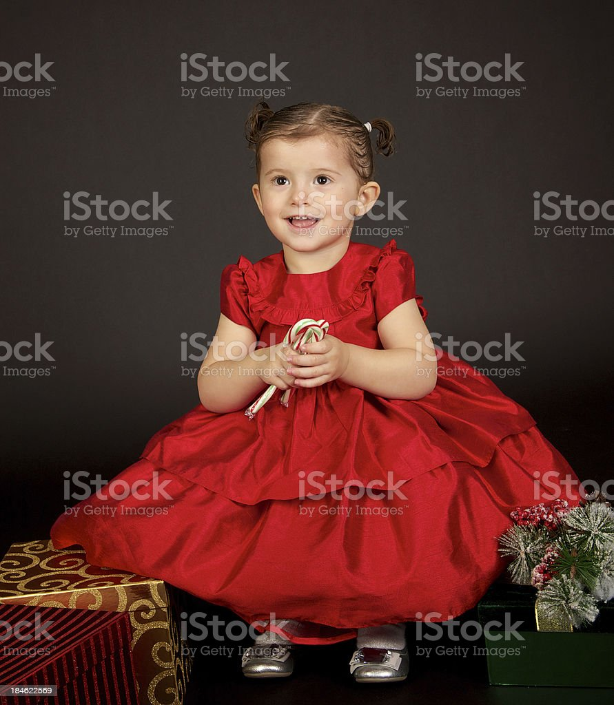 Adorable Christmas Girl in a Red Dress with Presents royalty-free stock photo