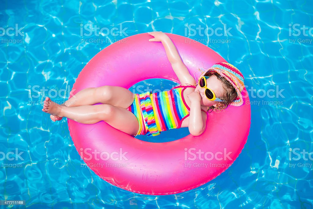 Adorable cute little girl playing in swimming pool stock photo