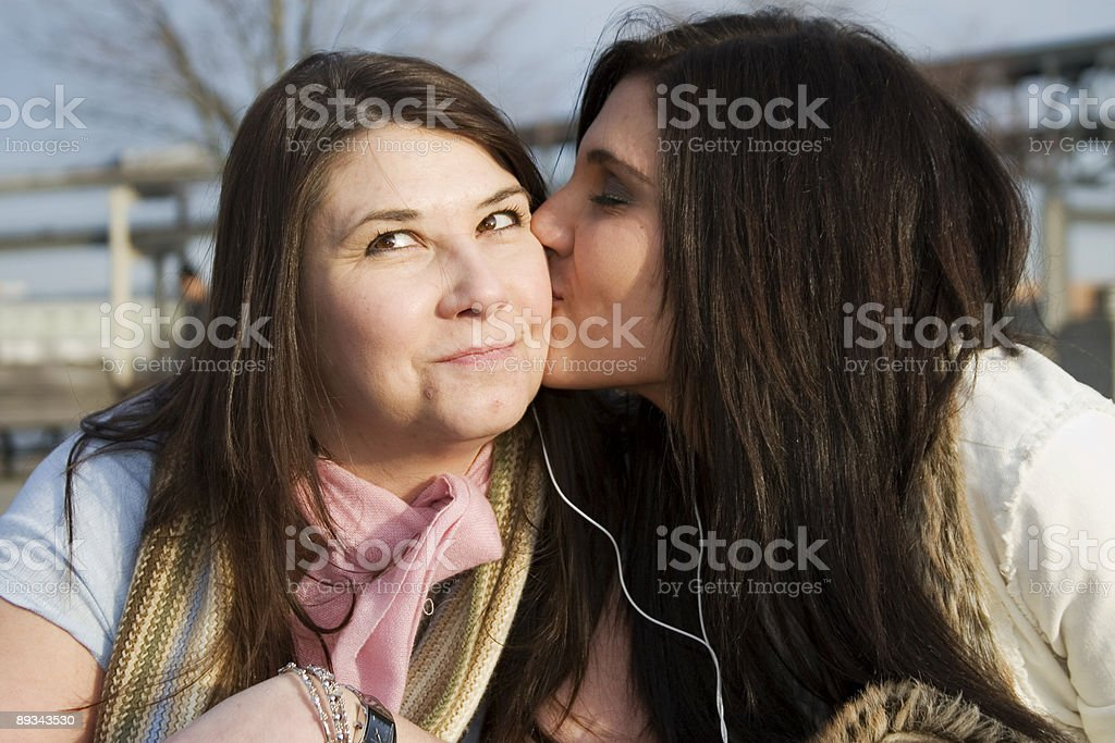 Adorable Daughter Kissing Cheek of Mother Outside, Smiling royalty-free stock photo