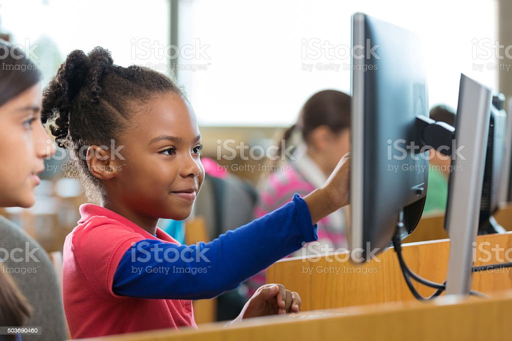 Adorable elementary age girls using computers in school library stock photo
