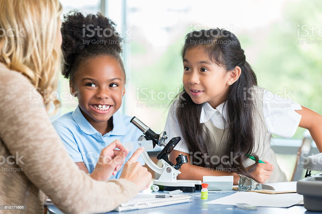 Adorable elementary schoolgirls enjoy working on science project with teacher stock photo