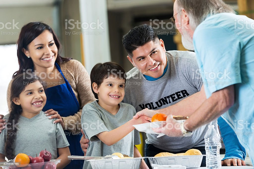 Adorable family volunteering in soup kitchen together
