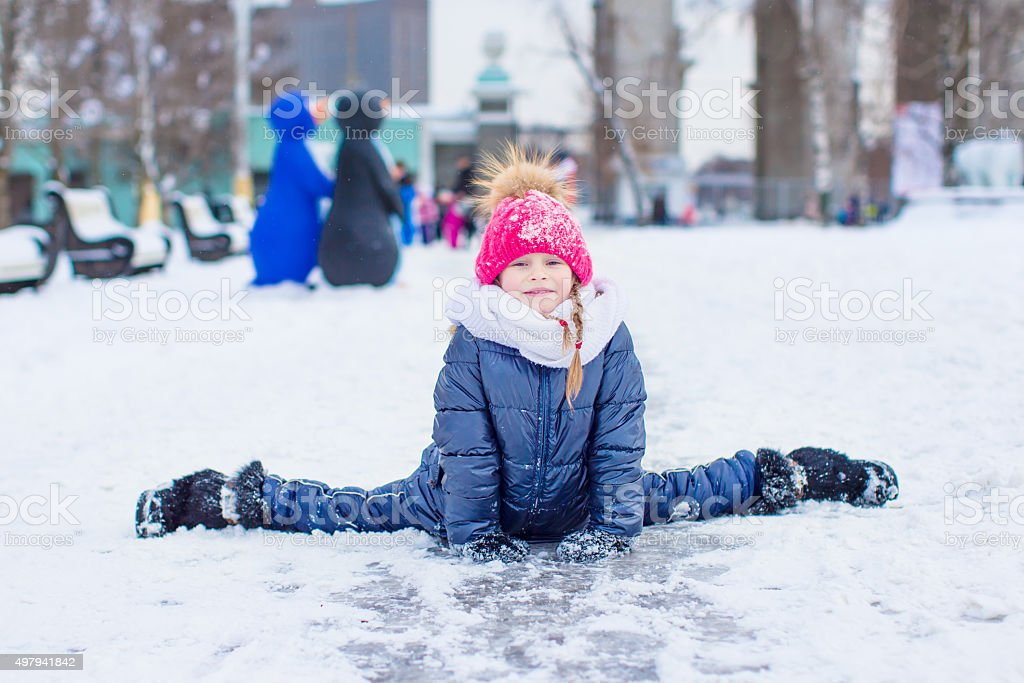 Adorable fashion little girl skating on the ice rink outdoors stock photo