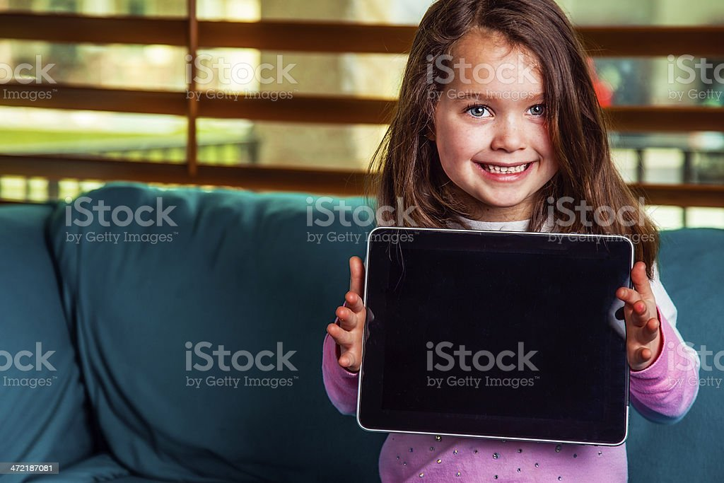 Adorable Female Child Displays Satisfaction with Electronic Tablet stock photo