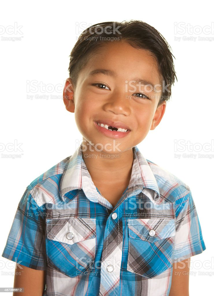 Adorable Filipino Boy Smiling with Two Missing Front Teeth stock photo