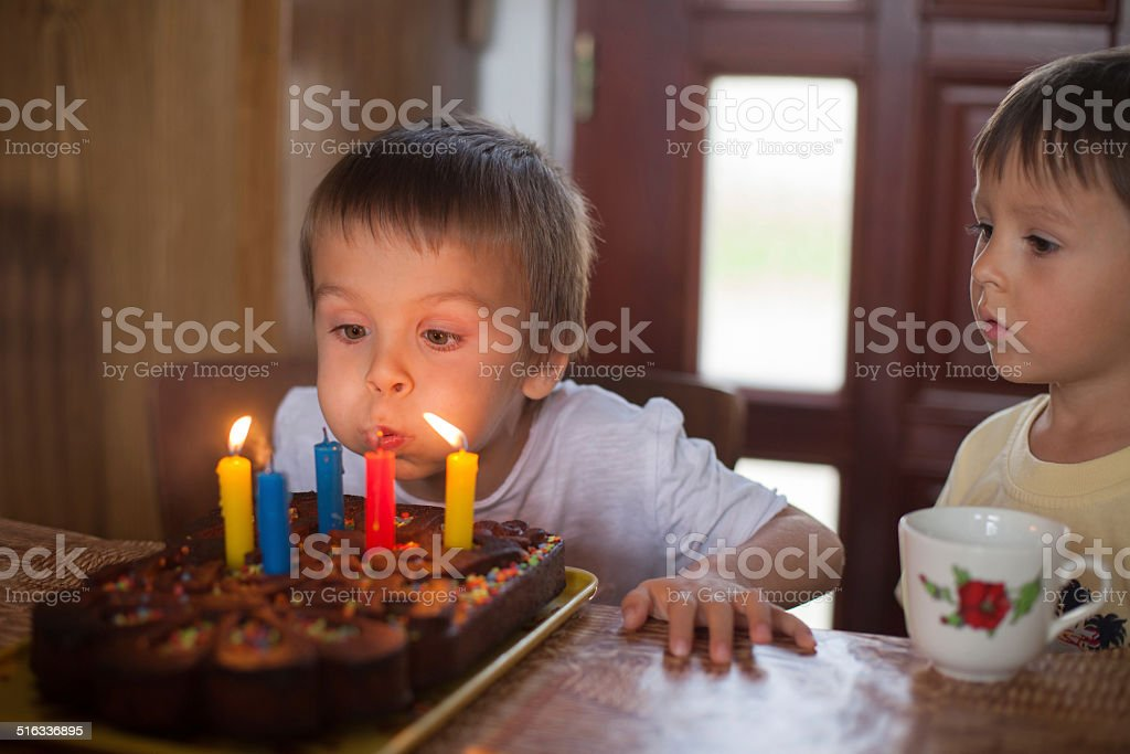 Adorable five year old boy celebrating his birthday and blowing stock photo