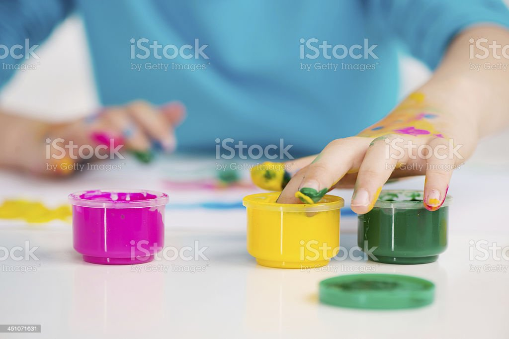 Adorable girl finger painting. stock photo