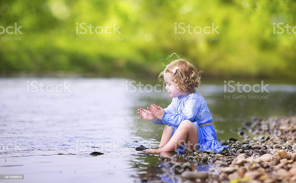 Adorable girl playing at river shore stock photo