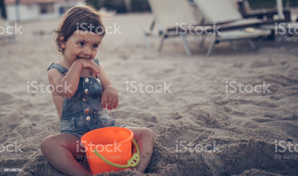 Adorable girl playing in sand stock photo