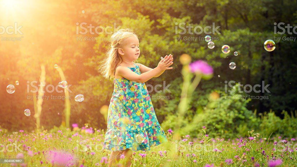 Adorable girl playing with soap bubbles during summer afternoon stock photo