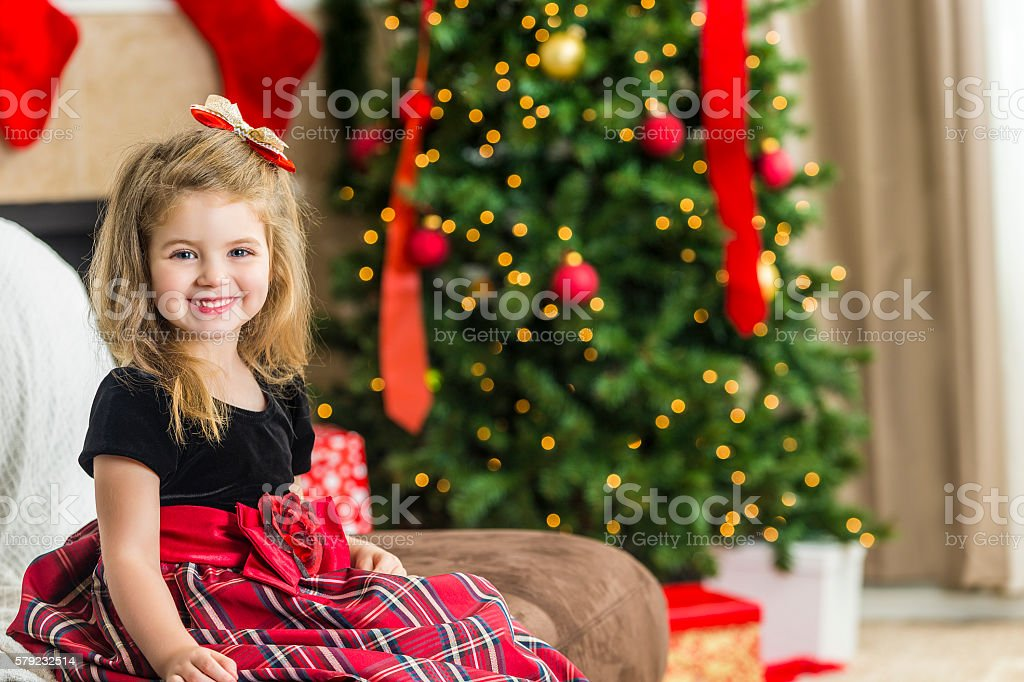 Adorable girl ready to open presents at a Christmas party stock photo