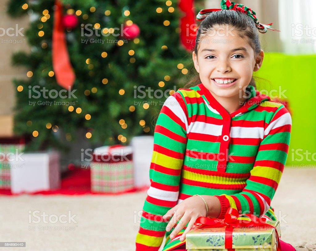 Adorable girl smiling in her Christmas pajamas stock photo