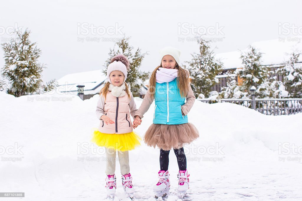 Adorable girls skating on ice rink outdoors in winter day stock photo