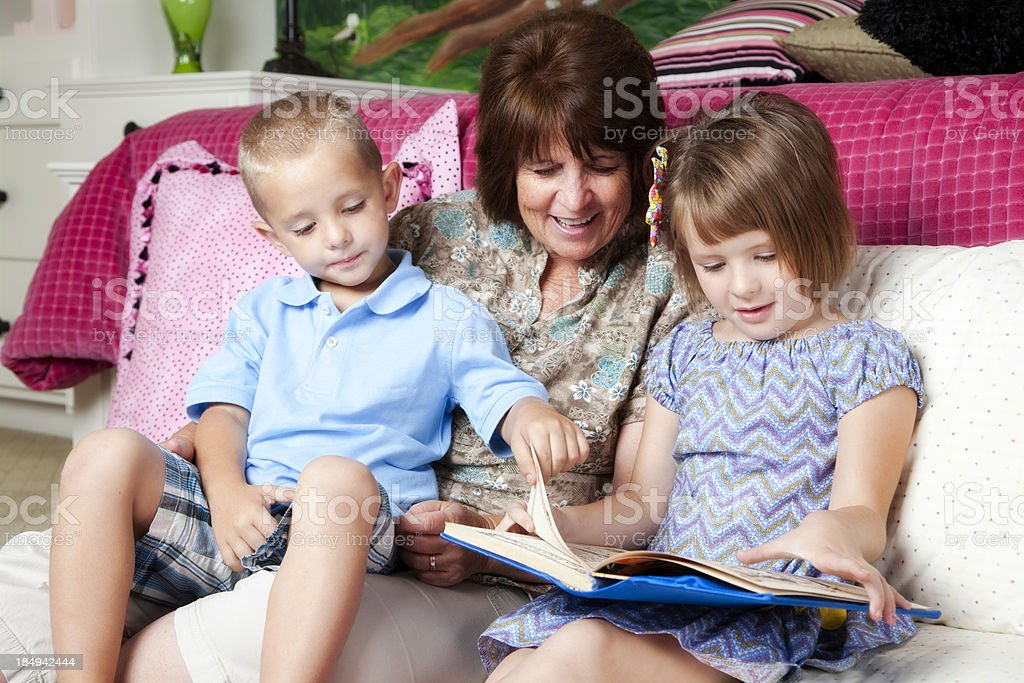 Adorable Grandchildren and Grandmother Reading Together royalty-free stock photo