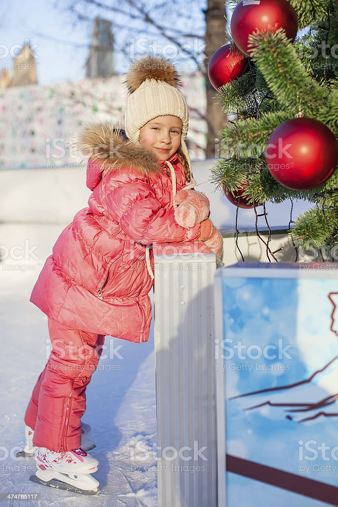 Adorable happy little girl enjoying skating at the ice-rink stock photo
