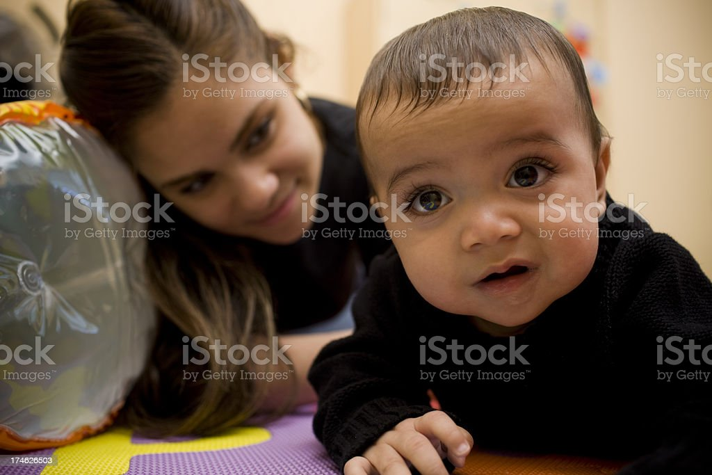 Adorable Hispanic Baby Boy Crawling with Mother in Playroom royalty-free stock photo
