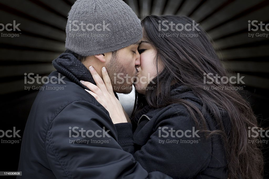 Adorable Hispanic Young Couple Kissing Outdoors in Winter royalty-free stock photo