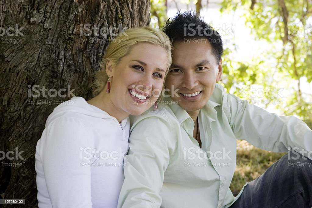 Adorable Interracial Young Couple Smiling, Cuddling Outside royalty-free stock photo