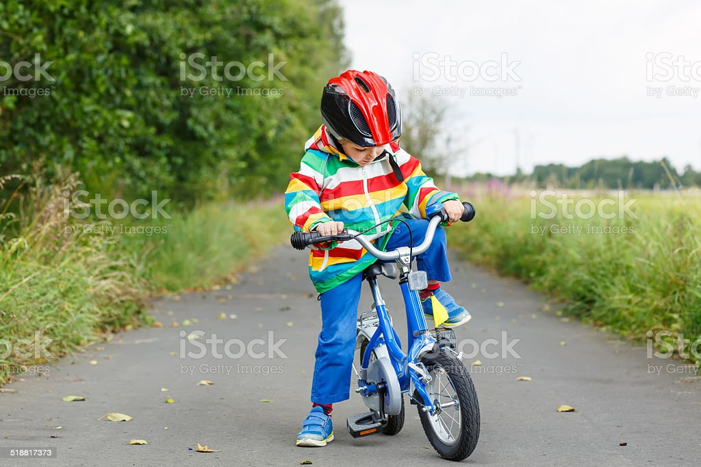 Adorable kid boy in helmet and colorful coat riding bike stock photo