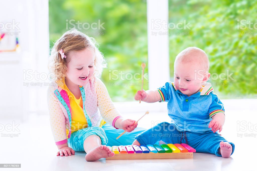 Adorable kids playing music with xylophone stock photo