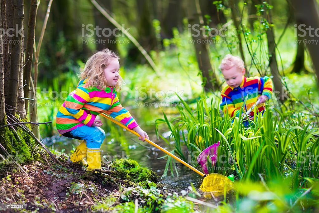 Adorable kids playing with frog stock photo
