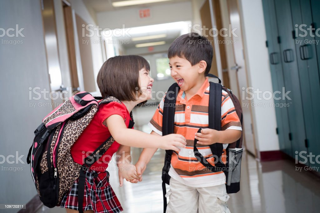 Adorable Kids with Backpacks Laughing in Elementary School Hallway stock photo