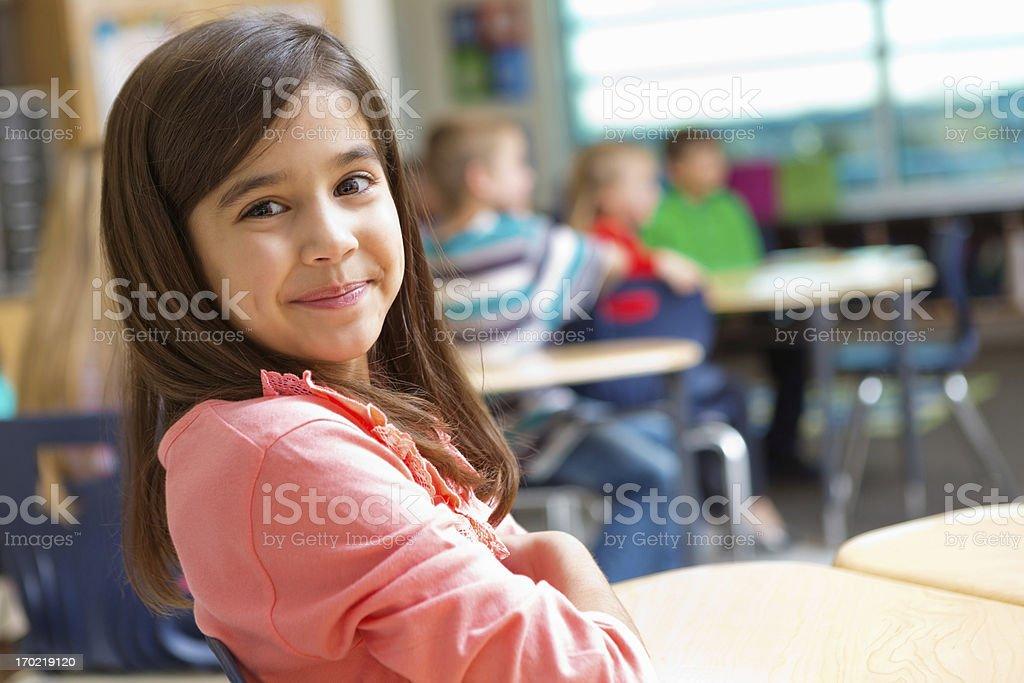 Adorable kindergarten or elementary school girl at desk in classroom royalty-free stock photo