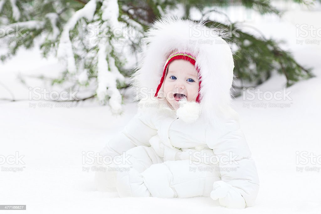 Adorable laughing baby sitting in snow under Christmas tree royalty-free stock photo