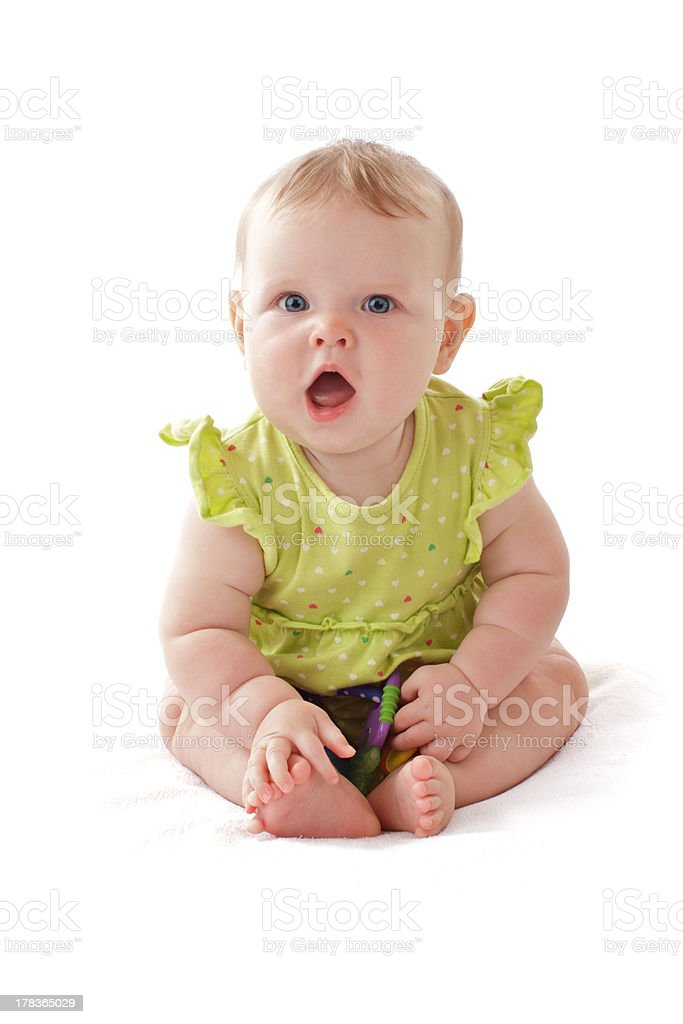 Adorable laughing blue eyed baby sits with her toy rattle. stock photo