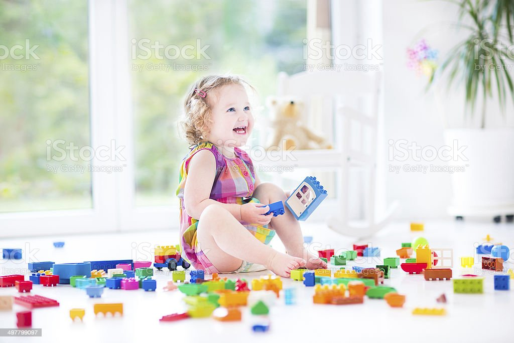 Adorable laughing toddler girl with colorful blocks sitting on floor stock photo