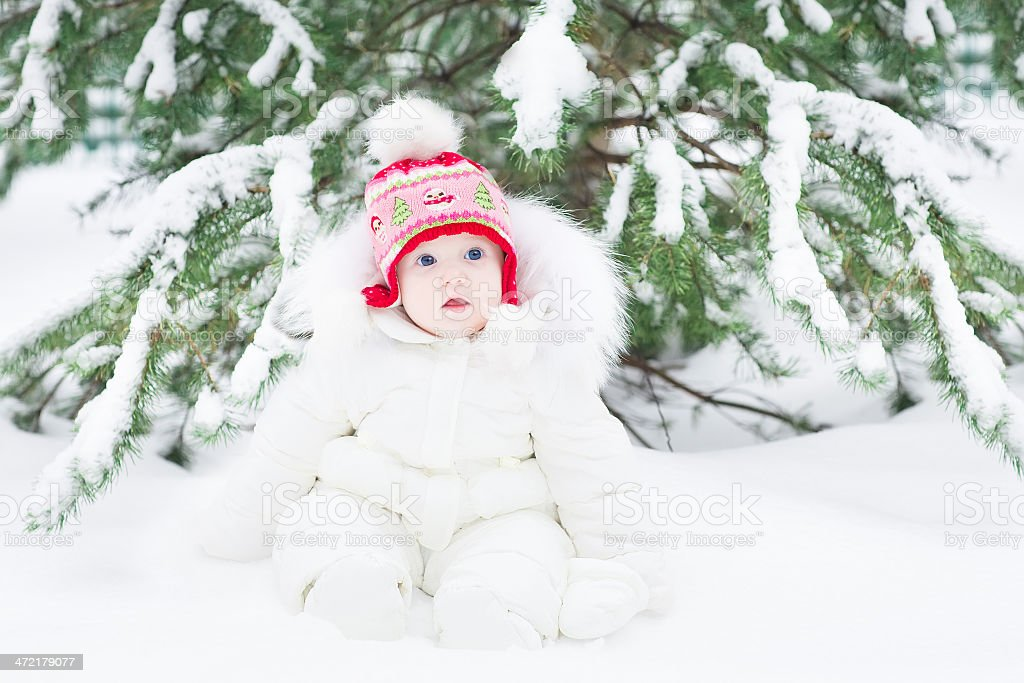 Adorable little baby playing in snow into winter park royalty-free stock photo