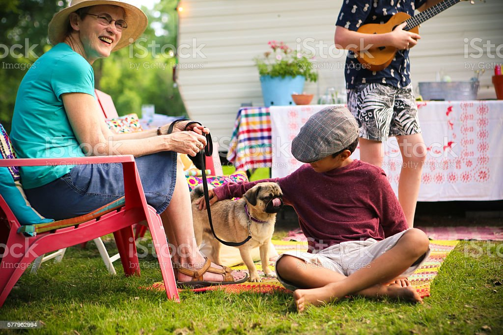 Adorable Little Boy and Pug Dog Camping with Friends stock photo