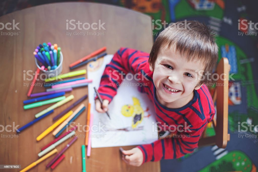 Adorable little boy, drawing picture for easter stock photo