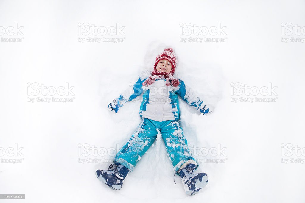 Adorable little boy in blue jacket, red hat and scarf stock photo
