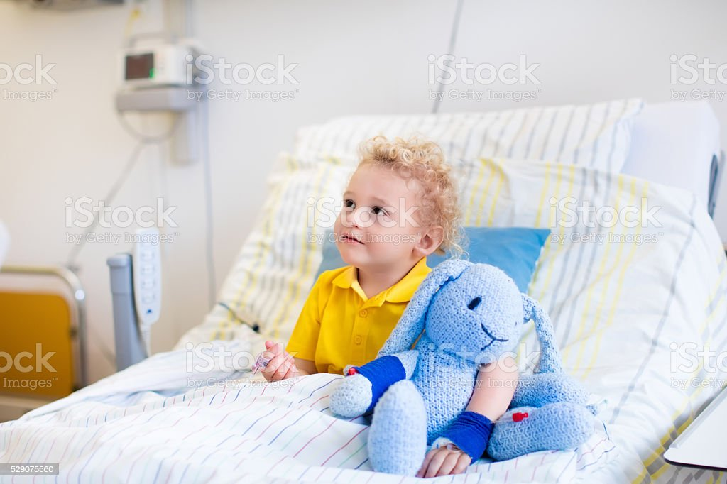 Adorable little boy in hospital room stock photo