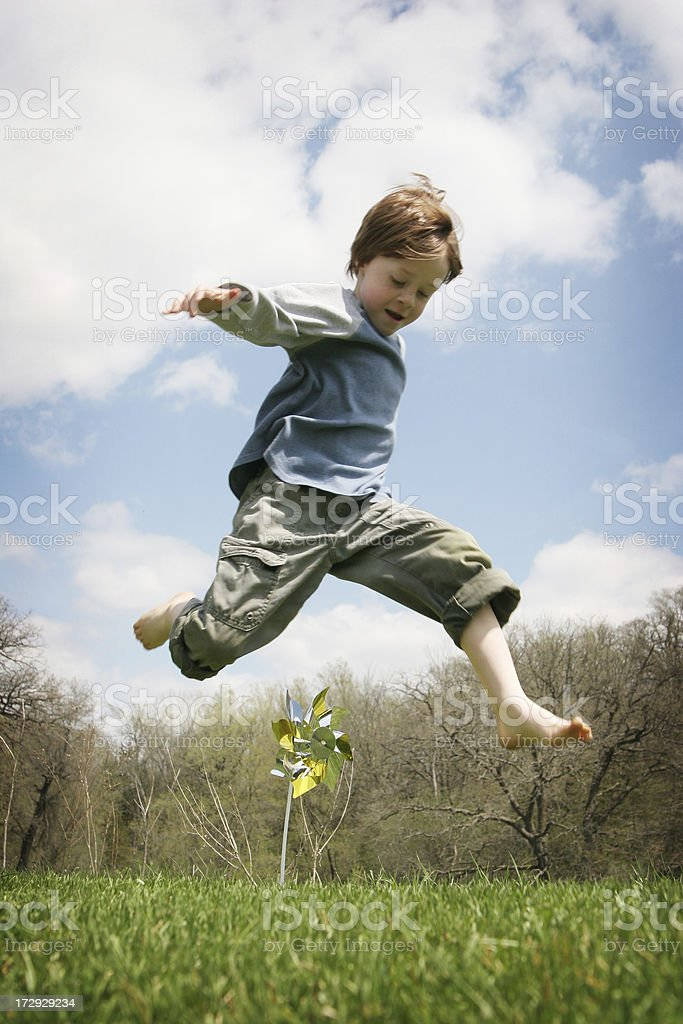 Adorable Little Boy Jumping Over Pinwheel- I Can Fly! royalty-free stock photo