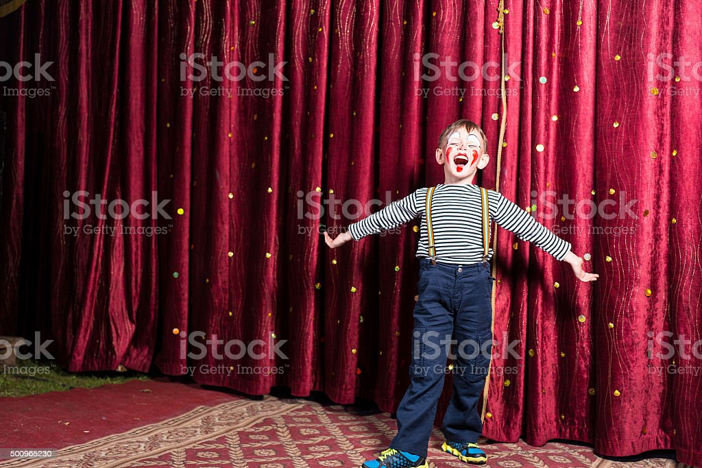 Adorable little boy singing on stage during a play stock photo