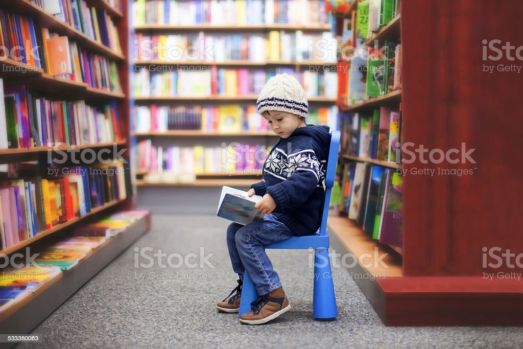Adorable little boy, sitting in a book store stock photo