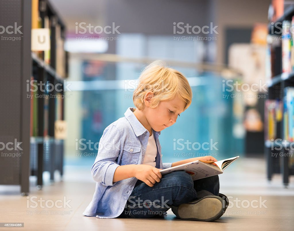 Adorable Little Boy Sitting In Library stock photo