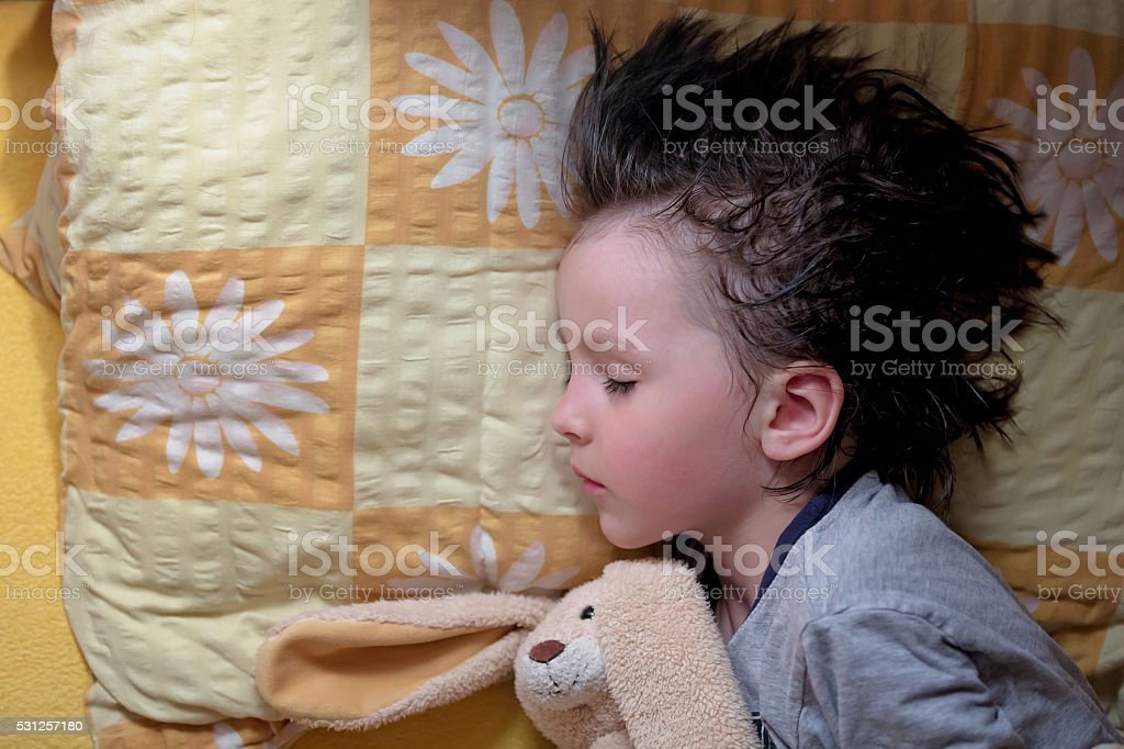 Adorable little boy, sleeping at night with his teddy bear stock photo