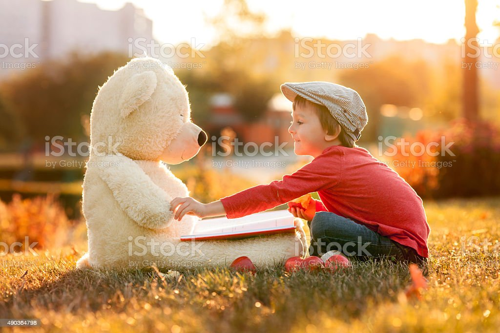 Adorable little boy with teddy bear friend in park stock photo