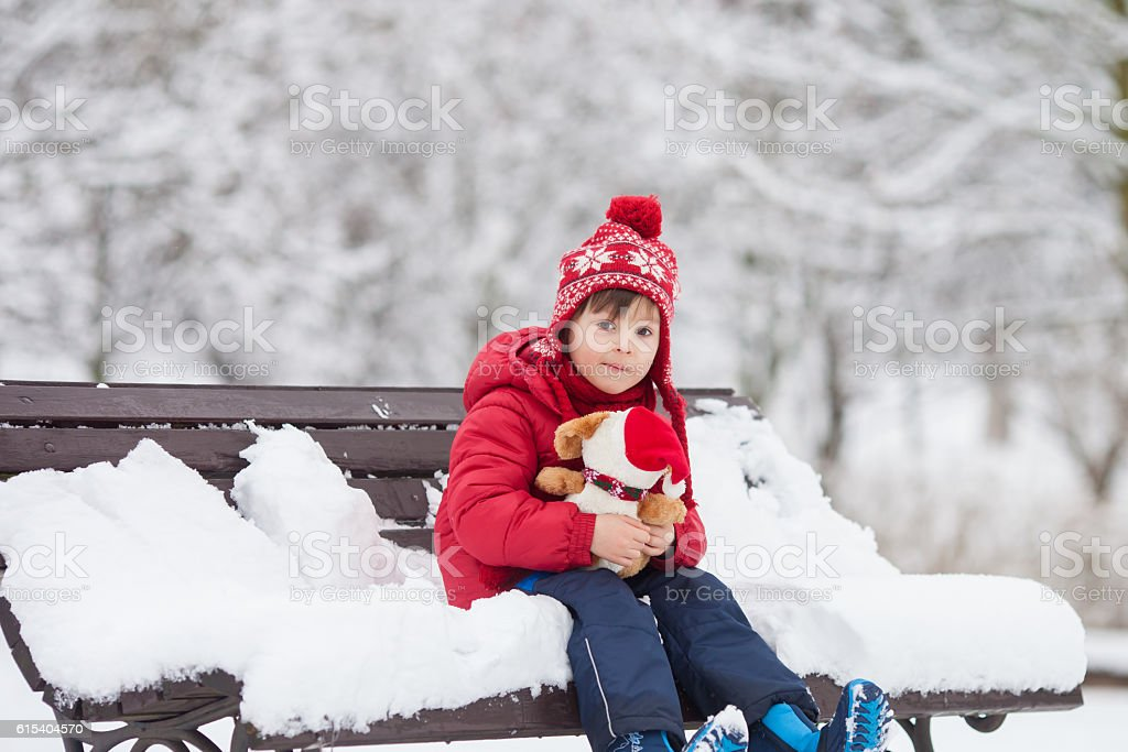 Adorable little child, boy, playing in a snowy park stock photo