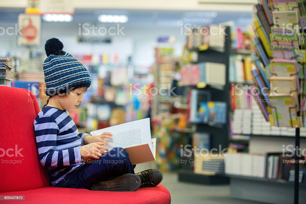 Adorable little child, boy, sitting in a book store stock photo