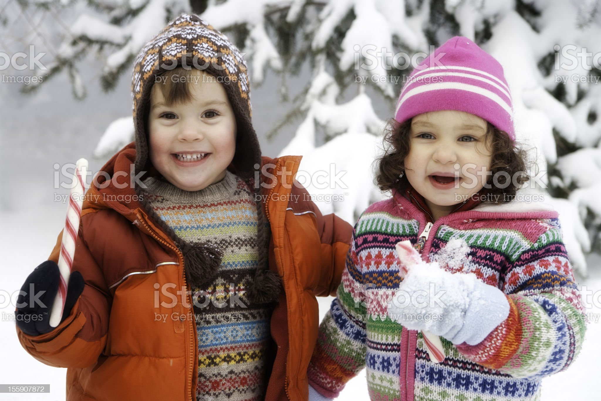 Adorable Little Girl and Boy Playing in the Snow Together royalty-free stock photo