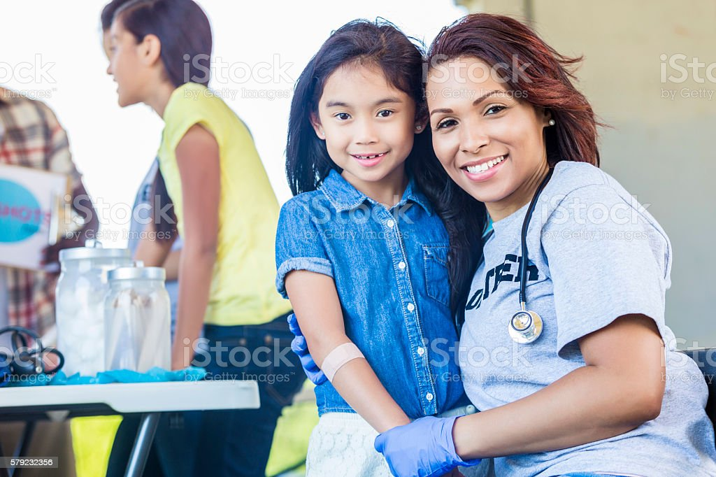 Adorable little girl being held by a volunteering nurse stock photo